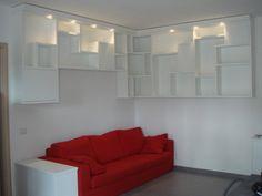 Libreria in stile moderno ad angolo e sospesa per soggiorno laccato bianco opaco con faretti a led, ante push pull e piani sfalsati.