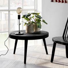 Rundt salongbord i kryssfinér med sort betongcoating. Beina i sortmalt mangotre skaper en helhetlig og ren look.