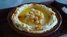 mashed chickpeas blended with tahini, olive oil, lemon juice, salt and garlic  As an appetizer and dip, hummus is scooped with flatbread, such as pita. It is also served as part of a meze or as an accompaniment to falafel or eggplant. Garnishes include chopped tomato, cucumber, coriander, parsley, caramelized onions, sautéed mushrooms, whole chickpeas, olive oil, hard-boiled eggs, paprika, sumac, ful, olives, pickles and pine nuts