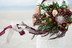 Flowy and elegant wedding bouquet with king protea, garden roses, agonis and ruscus. Love the winter, beach wedding look with dark reds, greens and an unexpected pop of peach.  Bunches & Blooms, Seattle Washington - burgundy bridal bouquet
