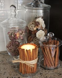 I like this idea of putting fall ingredients like cinnamon sticks in display vases, and I bet wrapping a candle in cinnamon makes the room smell so cozy when you burn it