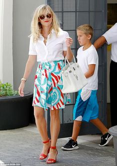 Reese Witherspoon's office chic: a flirty red, white and blue beach-ball print skirt and a tucked in white button-up blouse with a crisp white Birkin and red wedge sandals http://dailym.ai/1AETHDi