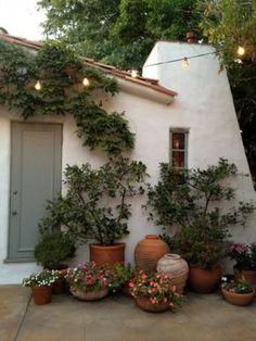 Mediterraanse tuin met heerlijk knusse warme sfeer.witte schuur terrac..potten 'grijze' schutting/poort en easy plants