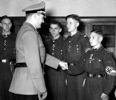 Artur Axmann the German Nazi national leader (Reichsjugendführer) of the Hitler Youth (Hitlerjugend) is seen here congratulating youth members for their combat service. Axmann lost his right arm during visit to the Eastern Front. After the war, he was found not guilty of war crimes and died in 1996, a free man.