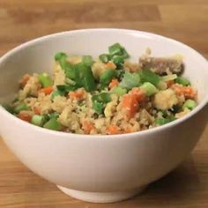 """Healthy Cauliflower Fried """"Rice"""" Here's what you need: - Cauliflower - 1 Tbsp. of sesame oil - 1 Tbsp. of garlic - 8 oz beef, chicken, pork, shrimp, or tofu - 1 cup of diced carrots - 1 cup of frozen peas - 2 eggs - White pepper to taste - 3 Tbsp. of soy sauce - Chopped green onions for garnish  Here's how you make it: Break down a head of cauliflower in a food processor until it's the size of rice. Heat sesame oil over high. Add garlic and fry until fragrant. Add the beef, chicken, pork…"""