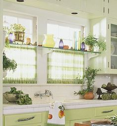 Fitted Kitchen Curtains for Privacy - Fabric panels shirred top and bottom onto tension rods cover the bottom half of these windows to provide privacy. A long glass shelf rests on brackets in front of the windows, offering a clever and efficient solution for displaying collectibles and plants.