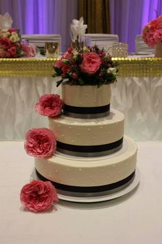 Simple single dot design wrapped with a double ribbon and accented with fresh flowers. www.mitchels.ca #wedding #weddingcakes #simple #flowers