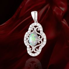 Elegant pendant with Opal center stone has arabesque filigree setting surrounded by a halo of sparkling accents. The setting is enhanced by a high polished bail and the exquisitely finished filigree d