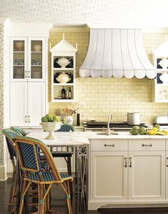 Inspired by French brasseries, designer John Oetgen paired a yellow tile backsplash with a zinc range canopy in the kitchen of this Atlanta house.