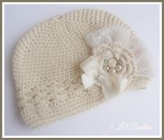 """"""" Maize """"  This beige crochet kufi cap features a soft ivory lace backdrop with an ivory crochet flower and faux pearl and satin ivory rose embellishment. The satin bow with rhinestone slider provides a sweet touch of sparkle.   This embellishment is attached to a clip so it can be removed for laundering purposes.   Find Maize Here : http://4lildarlins.com/catalog.php?item=669"""