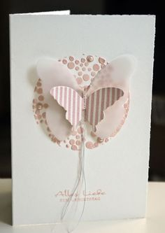 handmade card ... butterfly medallion ... matted circle covered with stenciled colored circles of embossing paste  ... layered butterfly in vellum and striped paper of the same dusty pink ... delightful card!