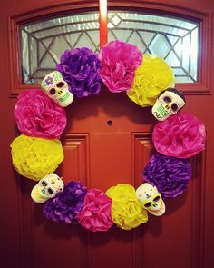 "Dia De Los Muertos Wreath!  Materials used:  -Handmade tissue paper flowers -Styrofoam skulls (from craft store)  -Puffy paint (to decorate skulls) -18"" wire wreath  -Hot glue"