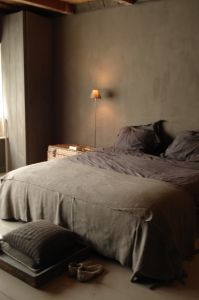 Plaster and timber, washed silk bedding, neutral palette