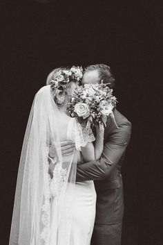 Black and white wedding portrait, kissing behind the bouquet.