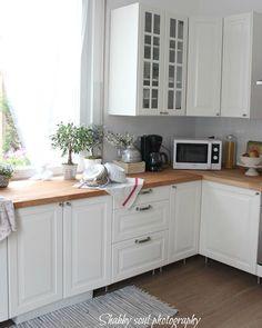 Butcher block counters, white cabinets, medium hardwood floor