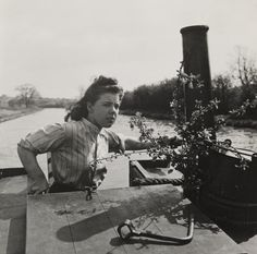 A photograph entitled 'Women run canal boats', taken in April 1945 by F Greaves for the Daily Herald. A woman steering a canal boat.