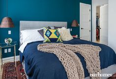 """A large walk-in closet, complete with drop-down ironing board, opens off the master bedroom. Oriental carpet, textural bedding and a colourful feature wall (Teal, Benjamin Moore) make the room warm and inviting.   See more of this home in """"Historic Home Converted to Condos Blends with New"""" from OUR HOMES London Summer 2016 http://www.ourhomes.ca/articles/build/article/historic-home-converted-to-condos-blends-with-new"""