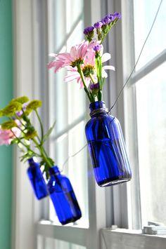 I am in love. Cobalt blue bottles as window garland. Amazing.