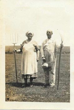 I love this picture. Farmer and wife with pitch forks. 1930's