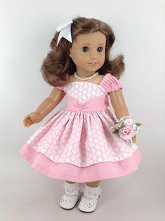 Handmade dress, petticoat, and pearl necklace for American Girl and other similar 18-inch dolls. This sweet cotton dress in colors of pink and white is made of cotton. Features include a lined bodice, a rounded front neckline and low-cut square back neckline, gathered cap sleeves with