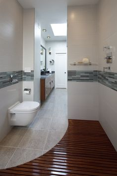 This curved, teak deck is disguising a free-form shower pan and drain that's sitting below the level of the floor instead above the floor as is the case in most bathrooms.