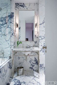 Marble Bathroom | A Greenwich Village pied-a-terre provides designers to the stars Waldo Fernandez and Tommy Clements the opportunity to live the simple life in very high style. The sconces are by Ozone, the bathroom vanity and tub are by Waterworks, and the fittings are by Lefroy Brooks. The walls are sheathed in Calacatta Viola marble. | www.elledecor.com #bathroom #luxurybathroom #bathroomlighting #luxuryfurniture #interiordesign #luxurydesign #homedecor #designdetails