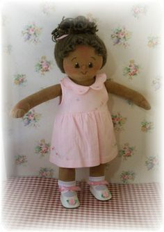 Handmade doll. This is Brooklyn.. She has a medium African American skin tone, brown eyes and brown curly hair worn in a pony tail.. She's very pretty in pink!