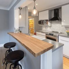 concrete counter w accent bar using wood counter. keeps it from being too cold/ modern w the white cabinets