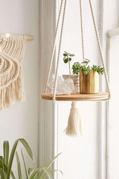 """Simply designed rope plant hanger by Recycled Lovers based in San Diego, California. Featuring a round stained wooden base, perfect for displaying your favorite trinkets and small potted plants. The 36"""" rope length makes it perfect for hanging near a window. Wood base measures 10"""" in diameter. Materials used: Cotton Rope, Wood"""