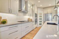 Ekko Kitchen #kitchen #white #medium Builder: Treehouse Developments Calgary; Designer: Jasmine Larre; Finish: Fusion Smooth White; Island Finish: Maple Tennessee