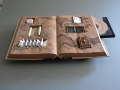 This altered book by Meg Kennedy, found on the New York Center for Book Arts artist website, is altered into a mini curio cabinet displaying forms of media, with a little stone tablet, scroll, accordion book / pamphlet, Japanese-bound book, chalkboard, codex, and CD drive inserted into the open text block. The book is transformed into a cabinet, a display case, a bookshelf, and a sculpture, and it's still a book.