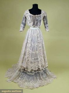 Haute Couture Victorian fashion lace tea dress gown from 1890-1920. #Historical #Costume in 19th century. Made from white dotted cotton net tulle with all over embroidered in flower floral garland embroidery and also trimmed with Battenburg lace, flounced net tulle lace and silk ribbon. Beautiful decollete, short sleeve design with lace underskirt. Decorative patterned in the front and the back of the skirt emerges into a long graceful train. #Vintage #Haute #Couture #Victorian #Fashion