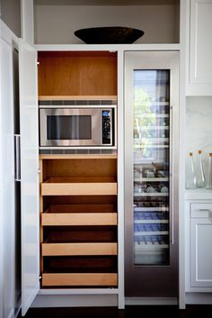 Microwave built-in to tall cabinet with roll-outs below.
