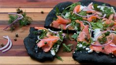 Recipe with video instructions: Enjoy lox with cream cheese on top of a deliciously briny squid ink flatbread. Ingredients: For the dough:, 1 ½ cups warm water, 2 ¼ tsp active dry yeast (1 packet), ½ tsp sugar, 3 ¼ cups all-purpose flour, 2 tsp salt, 2 tsp squid ink, olive oil, For the toppings:, ¼ lb sliced smoked salmon, 2 tbsp softened cream cheese, 1 cup arugula, ¼ cup red onion, thinly sliced, 1 tbsp small capers