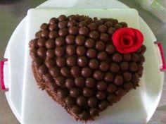 Torta de chocolate en forma de corazón con aplicación de una flor en Fondant