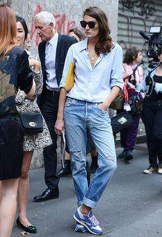 Look básico de street style: camisa azul e calça jeans com tênis confortável.