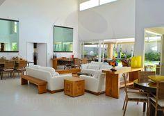 O amplo salão principal com pé direito duplo é bem arejado e bem iluminado, especialmente durante o dia, graças à enorme área envidraçada que faz com que a luz natural invada os três ambientes: o living room, a sala de jantar e a sala de TV.