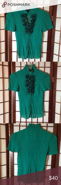 Gorgeous bebe Dressy Blouse Beautiful gem stone green blouse. Lots of floral appliqués. Very sexy and very comfortable. Semi-Sheer. 100% Silk. Dry clean only. In excellent used condition. Wore maybe once or twice at most. No rips, stains, tears or pulls. bebe Tops Blouses