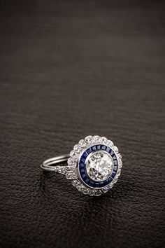 A beautiful Floral Estate Diamond Engagement Ring, set in stunning handmade platinum setting, and surrounded by a halo of sapphires and a halo of diamonds.