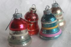 1940's ornaments. My mama had some just like these...in fact I still have the little turquoise one with the pink, yellow and white stripe around. Brings back many memories of Christmas past.