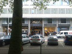 BINNEN - In dat gebouw staat een auto in de vitrine. Laat het lekker buiten rijden, arm ding.