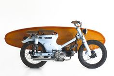 The Little Blue C70 by Deus Ex Machina. A beautifully chopped 1976 Honda Cub by the guys in Bali. Complete with surfboard. What cheerful way to ride to the beach.