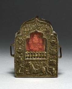 Case (amulet) with plaque (Tsa Tsa) and fragment wrapped in paper. Made of bronze. 2011 Sept – 2012 Feb, 'Grayson Perry: The Tomb of the Unknown Craftsman', BM Galleries, G35 Purchased from: H A Iggulden (along with many other items acquired during the Younghusband Expedition)
