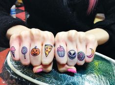 Lovely small tattoos on fingers: ice cream cone, lollypop, pumpkin head, a slice of a pizza, cupcake, scary face, doughnut and a crescent moon