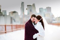 Mr & Mrs snuggle up on the Stone Arch Bridge on their chilly Minnesota winter wedding day! Photo by Eileen K Photography