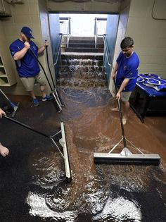 Kansas City Royals tarp crew members try to keep runoff from reaching the batting cages as water cascades from the dugout before the postponement of Monday's baseball game against the Tampa Bay Rays on July 6, 2015 at Kauffman Stadium in Kansas City, Mo.