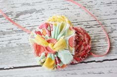 Sweet Little Meadow- frayed fabric ruffle and rosette headband. $13.50, via Etsy.