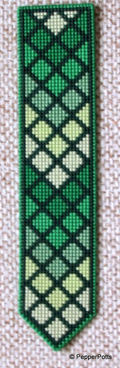 Worked on 14ct plastic canvas in a cross stitch, using various shades of green stranded cotton leftovers. The diamonds were worked first, then the contrasting lines filled in in a very dark green stranded cotton. It is backed with thin craft foam using a double sided adhesive film.