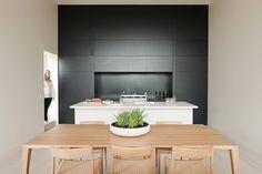 aménagement cuisine blanche, noire et bois ouverte sur la salle à manger