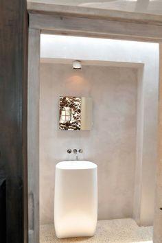 peinture à la chaux blanche, miroir mural et vasque sur pied blanche dans la salle de bains blanche